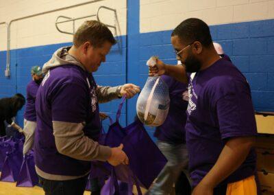volunteer puts turkey in food bag at event