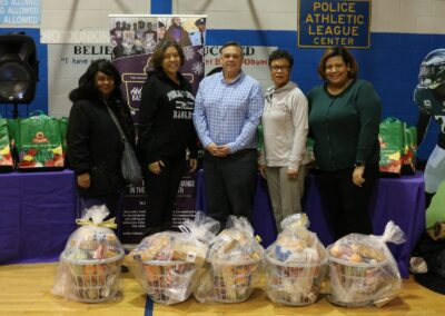 volunteers pose in front of food baskets at event