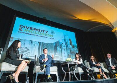 panelists on conference stage speak