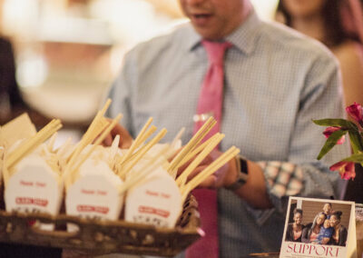 guest takes from offered tray of asian food cartons with chopsticks