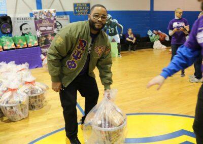 volunteer hands over food basket at event