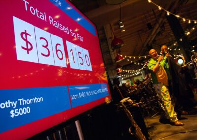 emcee celebrates $36k raised so far in front of digital board with live count