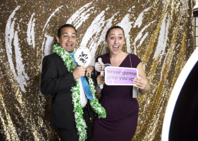 photobooth props are held up by smiling posing guests
