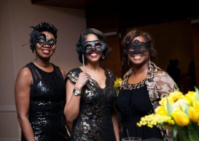 masked event guests smile together