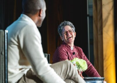panelists smile at each other on conference stage