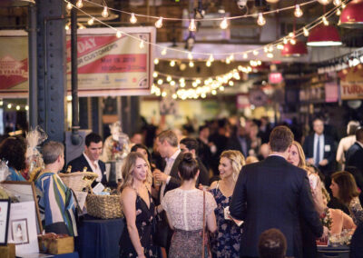 guests stand together smiling at vibrant event lit by warm string lights