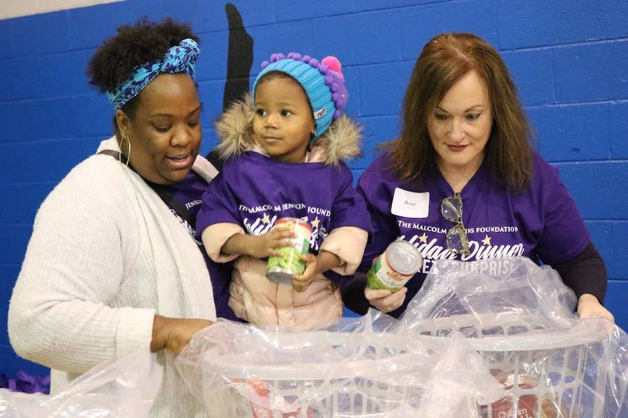 volunteers at holiday basket event smile, two women and a little girl