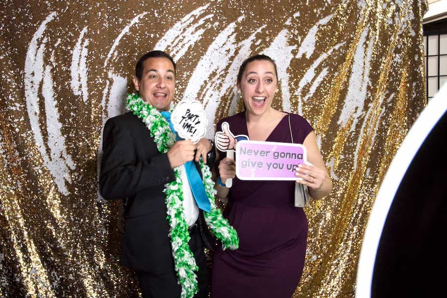 guests at an event smile in a photobooth with fun prop signs and feather boas