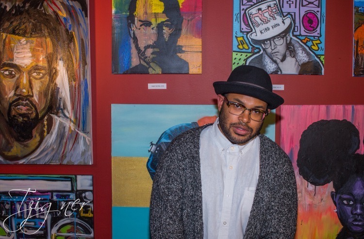 image of young artist standing in front of paintings