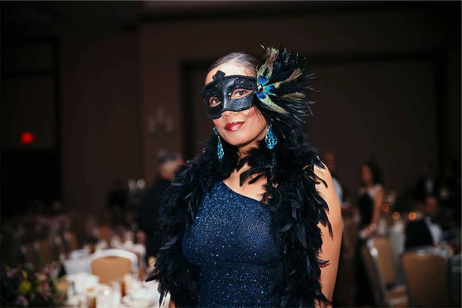 guest from party in feather boa and elaborate mask smiles and looks great